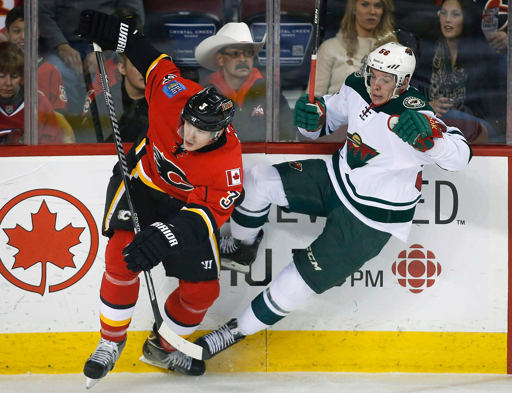 . Calgary Flames\' Ladislav Smid checks Minnesota Wild Erik Haula, right, during first period of an NHL hockey game in Calgary, Alberta, Saturday, Feb. 1, 2014. (AP Photo/The Canadian Press, Jeff McIntosh)