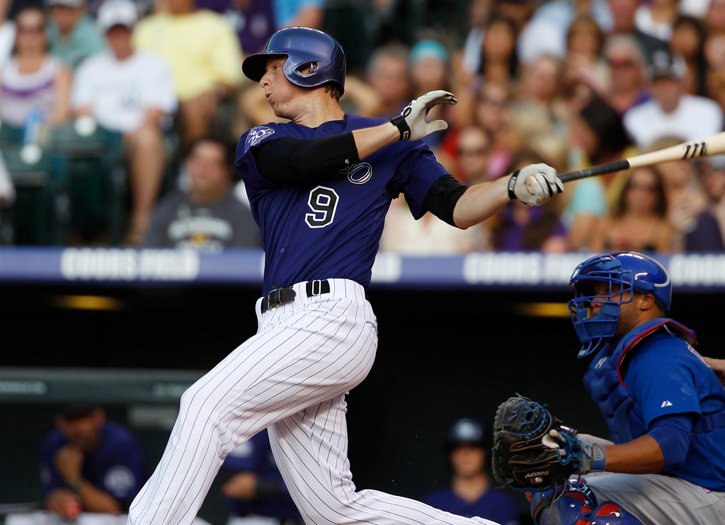 . Colorado Rockies\' DJ LeMahieu follows the flight of his single as Chicago Cubs catcher Wellington Castillo looks on in the first inning of a baseball game in Denver on Saturday, July 20, 2013, in Denver. (AP Photo/David Zalubowski)