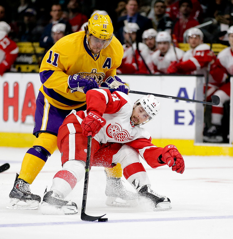 . Los Angeles Kings center Anze Kopitar (11) tries to push Detroit Red Wings left wing Tomas Tatar off the puck during the first period of an NHL hockey game in Los Angeles, Tuesday, Feb. 24, 2015. (AP Photo/Chris Carlson)