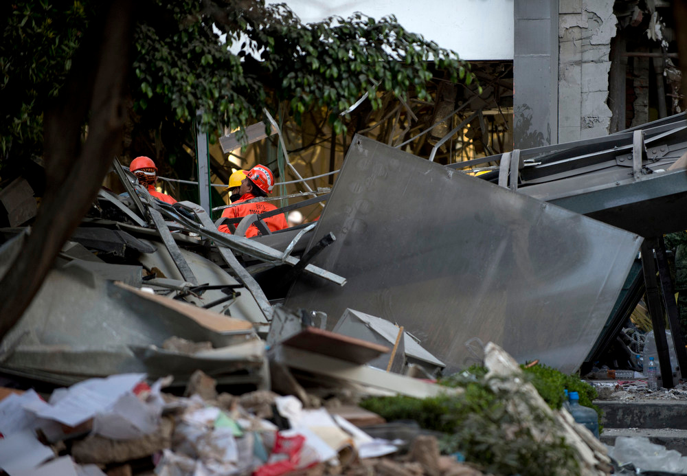 Description of . Rescuers search for victims  amid the debris at the headquarters of the state-owned Mexican oil giant Pemex in Mexico City on February 1, 2013, following a blast inside the building. An explosion rocked the skyscraper, leaving up to now 25 dead and 100 injured, as a plume of black smoke billowed from the 54-floor tower, according to official sources.  AFP PHOTO/ YURI CORTEZ/AFP/Getty Images