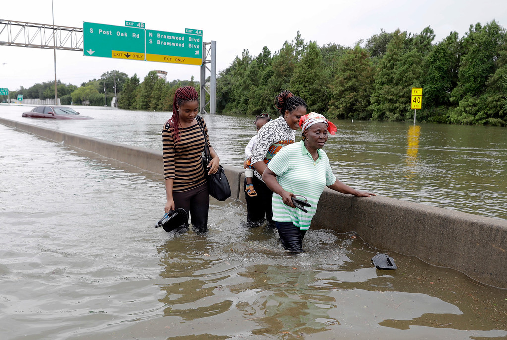 . Evacuees wade down a flooded section of Interstate 610 as floodwaters from Tropical Storm Harvey rise Sunday, Aug. 27, 2017, in Houston. The remnants of Hurricane Harvey sent devastating floods pouring into Houston Sunday as rising water chased thousands of people to rooftops or higher ground. (AP Photo/David J. Phillip)