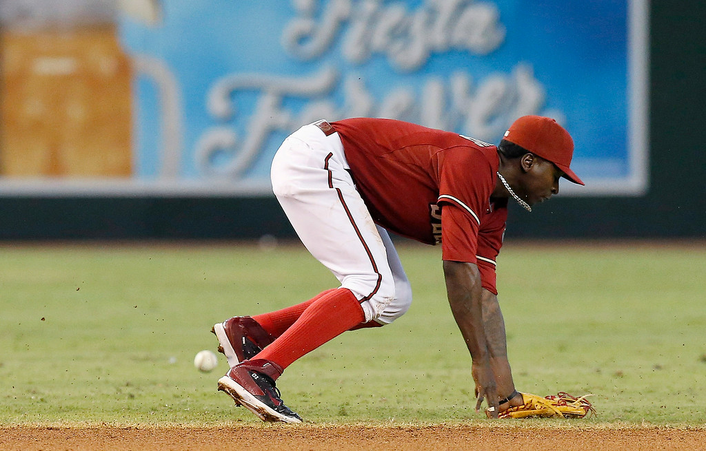 . Arizona Diamondbacks\' Didi Gregorius is unable to handle a grounder hit by Colorado Rockies\' DJ LeMahieu, for a single, during the fourth inning of a baseball game Sunday, Aug. 31, 2014, in Phoenix. (AP Photo/Ross D. Franklin)
