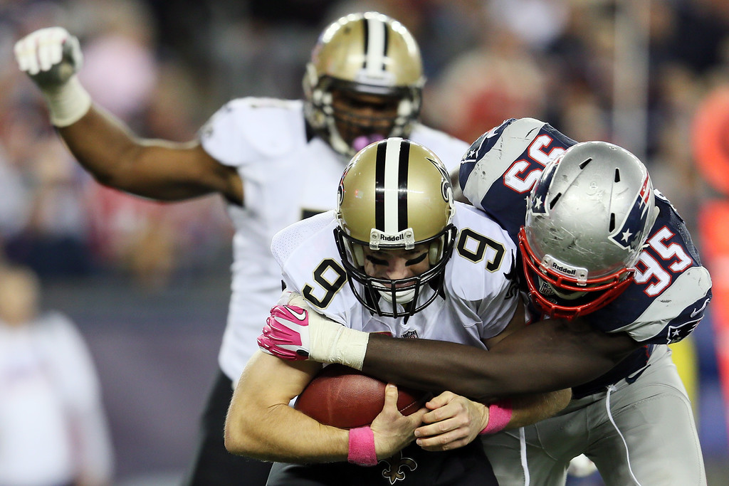 . Quarterback Drew Brees #9 of the New Orleans Saints is sacked by defensive end Chandler Jones #95 of the New England Patriots during the fourth quarter of the Patriots 30-27 win at Gillette Stadium on October 13, 2013 in Foxboro, Massachusetts.  (Photo by Rob Carr/Getty Images)