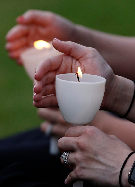 . Participants hold candles during the Mississippi Law Enforcement Memorial Candlelight Vigil by the Statewide Fallen Officers Memorial in Jackson, Miss., Tuesday, May 15, 2018. Fellow lawmen, family and friends participated in the service across from the Capitol. (AP Photo/Rogelio V. Solis)