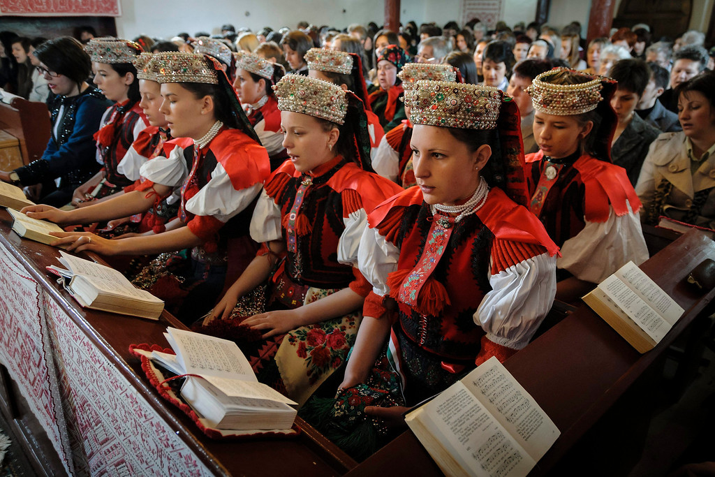 . Ethnic Hungarian girls wearing traditional folk costumes attend the Easter service in the Reformed church of the village of Sancraiu, Transylvania, North Western Romania, Sunday, April 20, 2014. (AP Photo/MTI, Zsolt Czegledi)