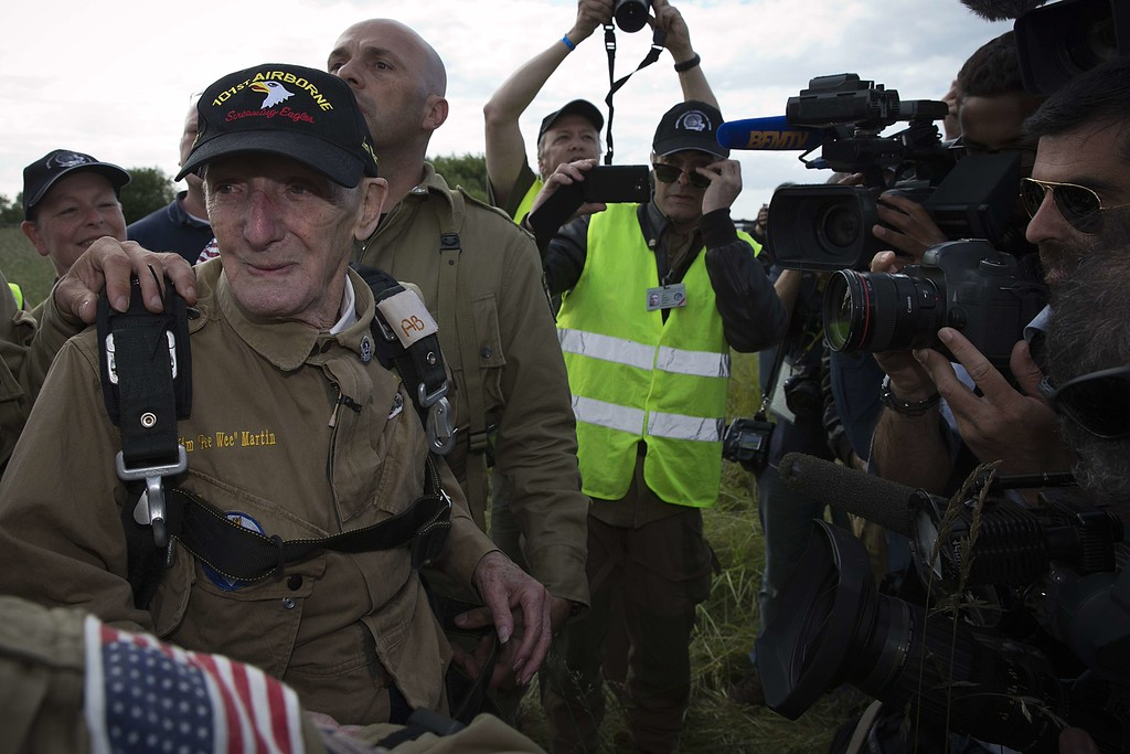 """. US war veteran Jim \""""Pee Wee\"""" Martin (L), 93, reacts after landing with a parachute on June 5, 2014 in Carentan, where he landed 70 years ago, when he was a paratrooper. The D-Day ceremonies on June 6 this year mark the 70th anniversary since the launch of \'Operation Overlord\', a vast military operation by Allied forces in Normandy, which turned the tide of World War II, eventually leading to the liberation of occupied France and the end of the war against Nazi Germany.  AFP PHOTO / JOEL SAGET/AFP/Getty Images"""