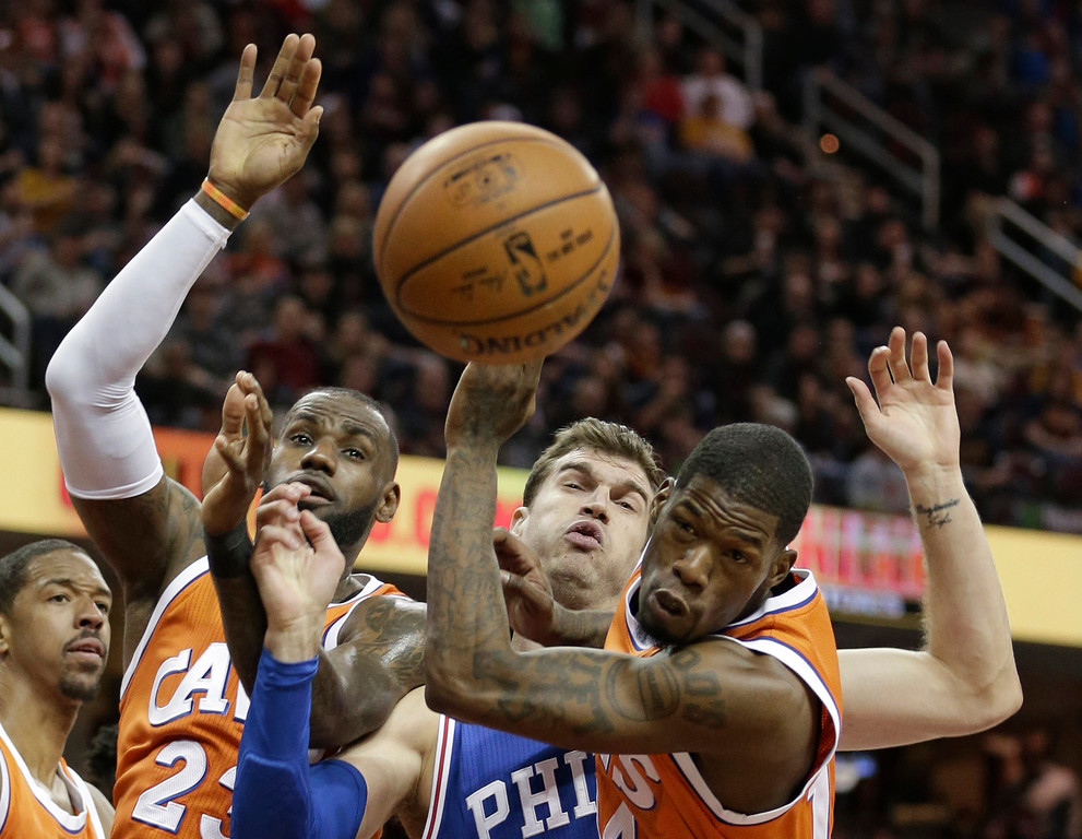 . From second from left to right, Cleveland Cavaliers\' LeBron James, Philadelphia 76ers\' Tiago Splitter and Cavaliers\' DeAndre Liggins battle for a rebound in the first half of an NBA basketball game, Friday, March 31, 2017, in Cleveland. (AP Photo/Tony Dejak)