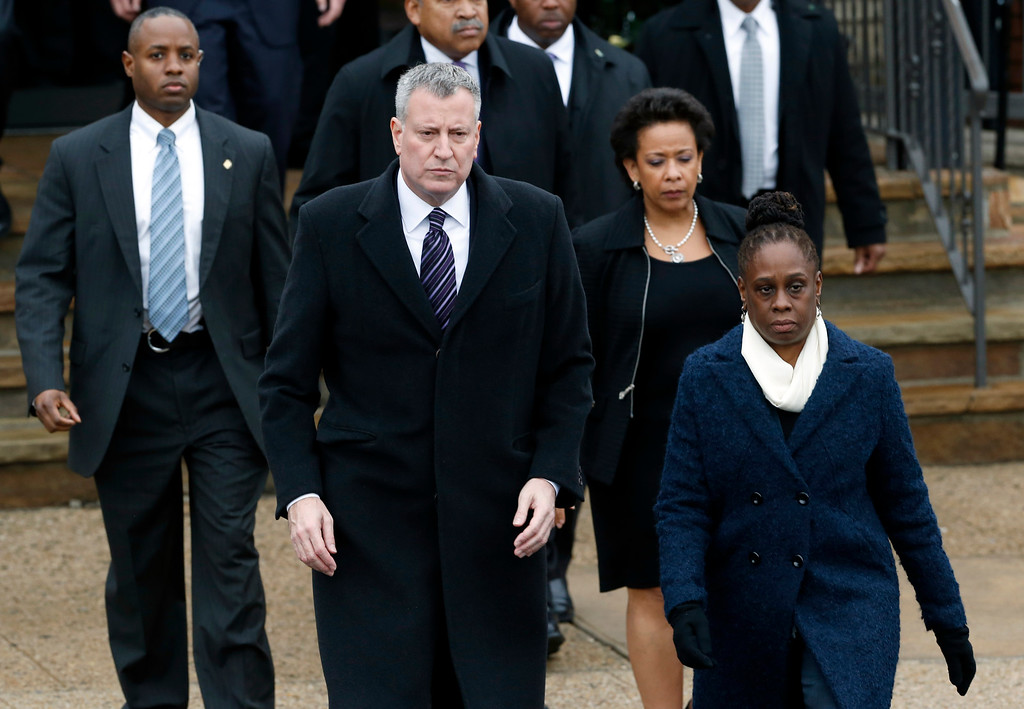 . New York City Mayor Bill de Blasio, center, walks with his wife Chirlane McCray, right, following funeral services for New York City police officer Wenjian Liu at Aievoli Funeral Home, Sunday, Jan. 4, 2015, in the Brooklyn borough of New York. Liu and his partner, officer Rafael Ramos, were killed Dec. 20 as they sat in their patrol car on a Brooklyn street. The shooter, Ismaaiyl Brinsley, later killed himself. (AP Photo/Julio Cortez)