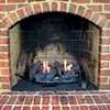 Close up of brick gas fireplace with a lit fire.