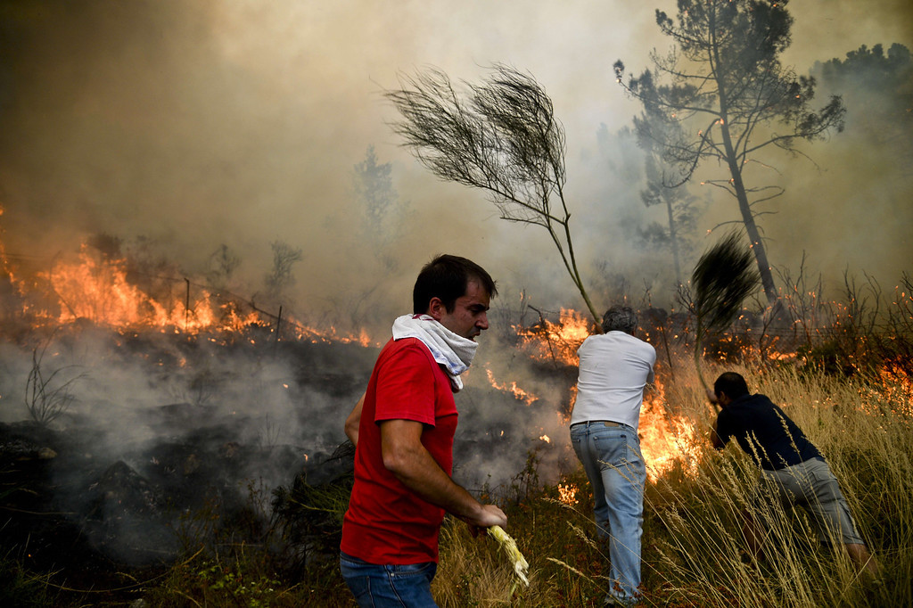 . Locals try to extinguish a wildfire in Caramulo, central Portugal on August 29, 2013. AFP PHOTO / PATRICIA DE MELO MOREIRA/AFP/Getty Images