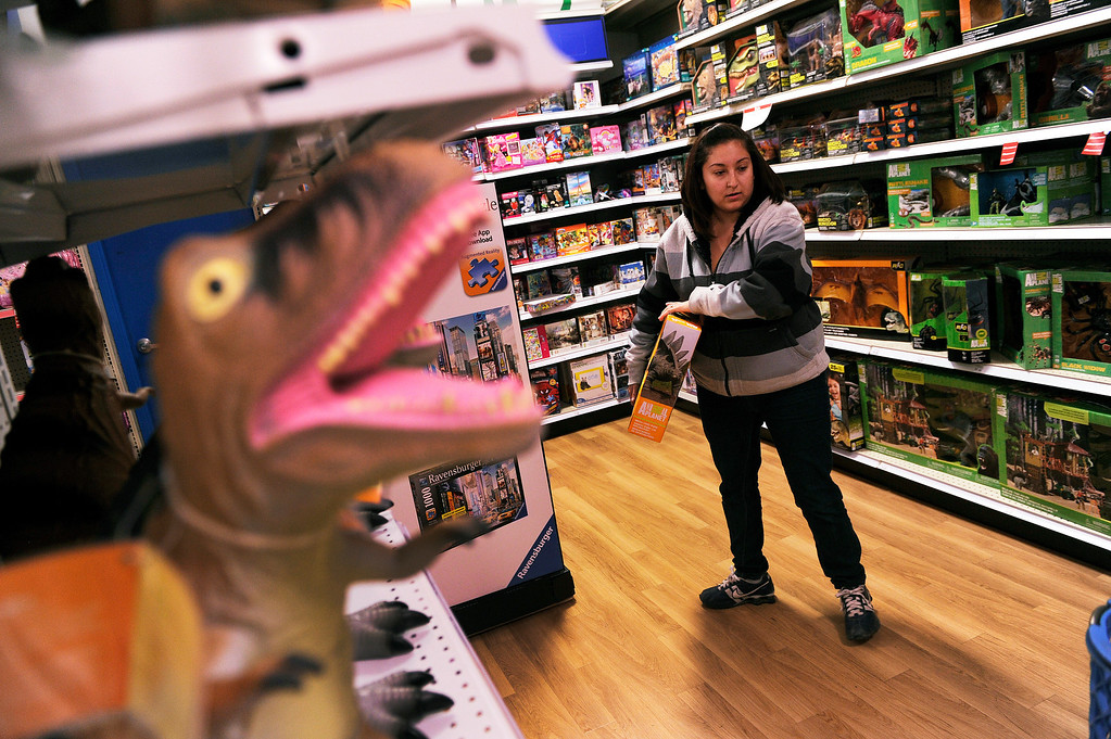 . Jennifer Martinez searched for items as she filled a cart with presents at the Toys R Us store on County Line Road in Arapahoe County Thursday night, November 28, 2013. Many metro area stores got a jump on Black Friday by opening Thanksgiving night. Photo By Karl Gehring/The Denver Post