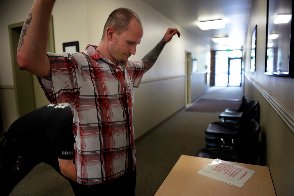. Parolee Thomas Vescio, 35, is patted down before his visit with his parole officer at Colorado Northeast Parole Office on July 25, 2013 in Westminster, Colorado.  (Photo By Joe Amon/The Denver Post)