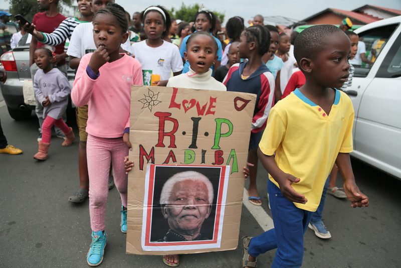 . Children carrying a placard walk along Vilikazi street outside late former South African president\'s Soweto home, where he lived with his wife Winnie Mandela, in Soweto, South Africa, 06 December 2013. Nobel Peace Prize winner Nelson Mandela died at age 95, in Johannesburg, South Africa, on 05 December 2013. A former lawyer, Mandela was the first black President of South Africa voted into power after the country��ôs first free and fair democratic elections that witnessed the end of the Apartheid system in 1994. Mandela was founding member of the ANC (African National Congress) and anti-apartheid activist who served 27 years in prison, spending many of these years on Robben Island. In South Africa, Mandela is often known as Tata Madiba, an honorary title adopted by elders of Mandela\'s clan. Mandela won the Nobel Peace Prize in 1993.  EPA/TJ LEMON
