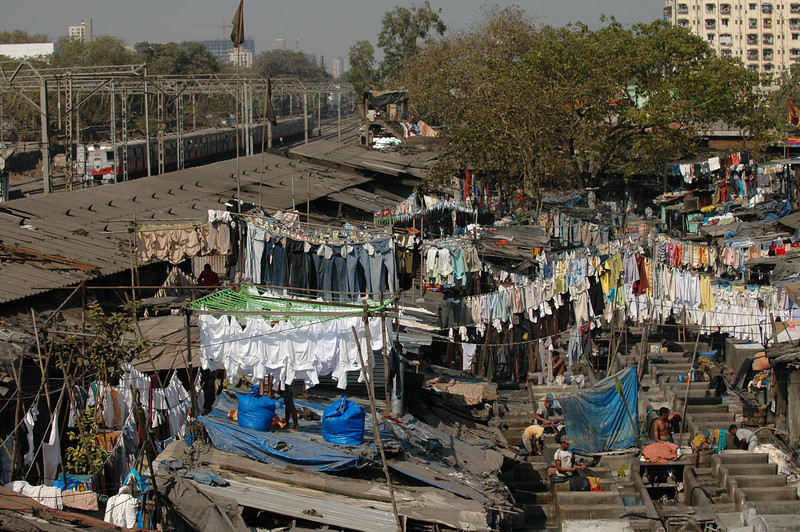 Washing clothes at Dhobi Ghat in Mumbai. A local train passes by in the background