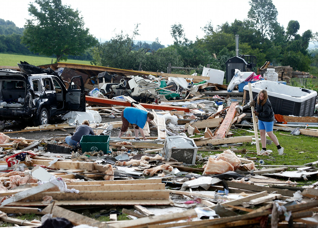 . People sort through debris of a destroyed house after Tuesday night\'s storm, on Wednesday, July 9, 2014, in Smithfield, N.Y. The National Weather Service has confirmed that a tornado destroyed the homes in upstate New York where four people were killed. (AP Photo/Mike Groll)