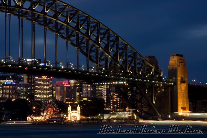 Sydney Harbor bridge at dusk.  Luna park is the amusement park under the bridge.