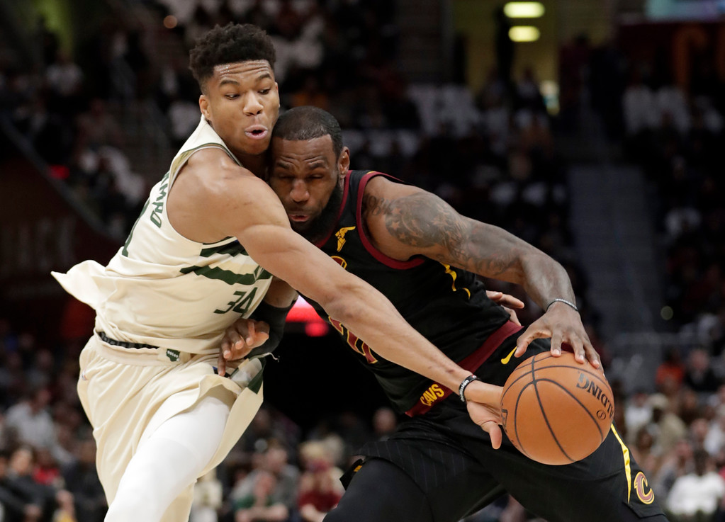 . Milwaukee Bucks\' Giannis Antetokounmpo, left, from Greece, knocks the ball loose from Cleveland Cavaliers\' LeBron James in the first half of an NBA basketball game, Monday, March 19, 2018, in Cleveland. (AP Photo/Tony Dejak)