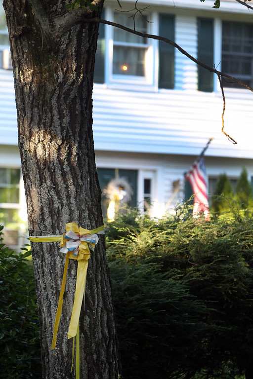 . A ribbon is tied to a tree outside the home of American freelance journalist James Foley, on Tuesday Aug. 19, 2014, in Rochester, N.H. A video by Islamic State militants that purports to show the killing of Foley by the militant group was released Tuesday. (AP Photo/Jim Cole)