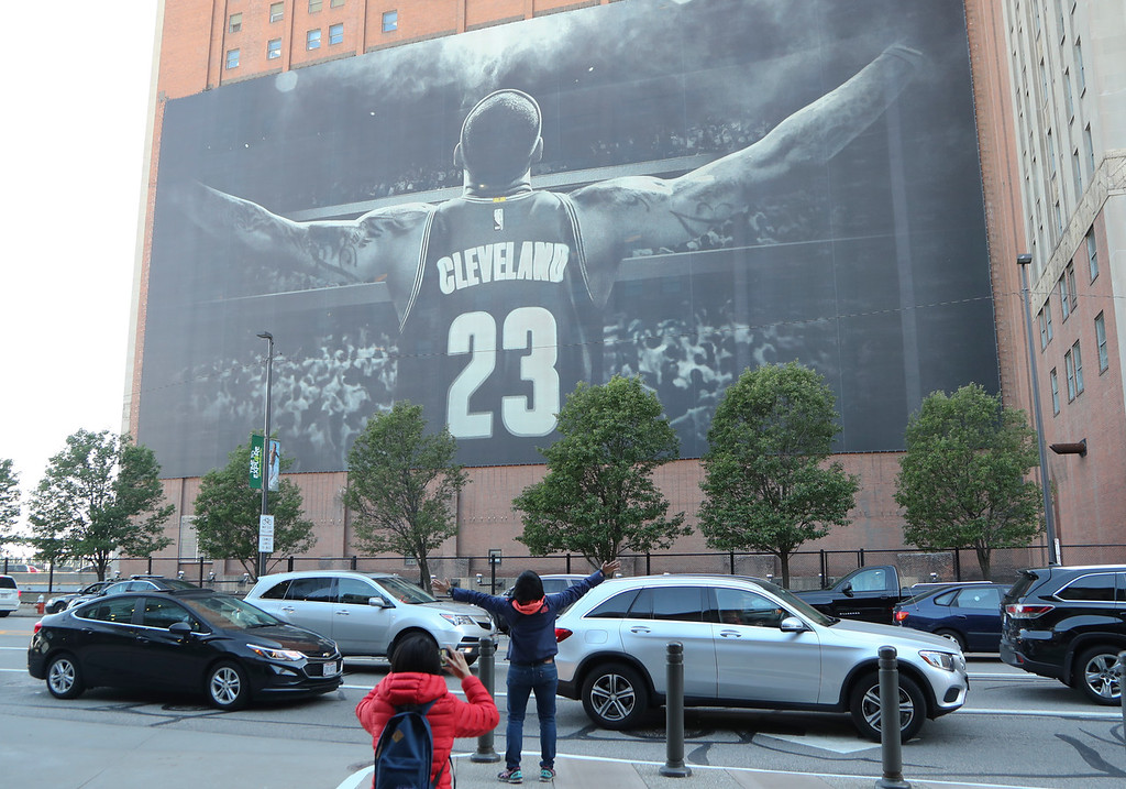 . A fan poses for a photo in front of a mural of Cleveland Cavaliers forward LeBron James (23) before Game 3 of basketball\'s NBA Finals between the Cavaliers and the Golden State Warriors, Wednesday, June 6, 2018, in Cleveland. (AP Photo/Carlos Osorio)