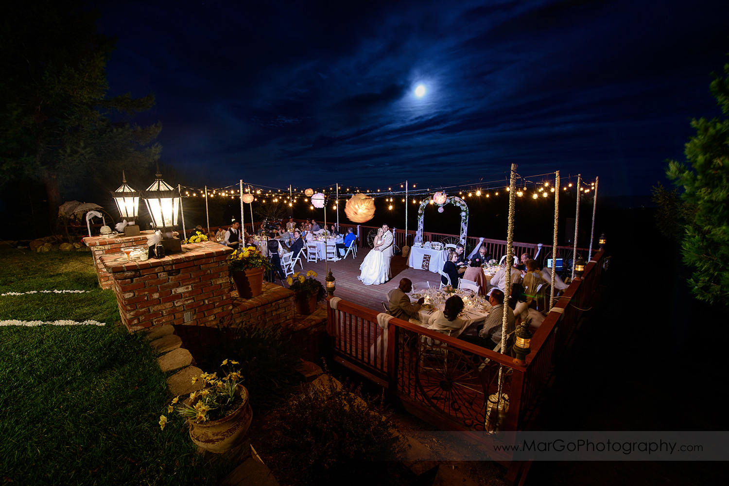 night shot of bride and groom standing in the middle of dance floor during backyard wedding reception