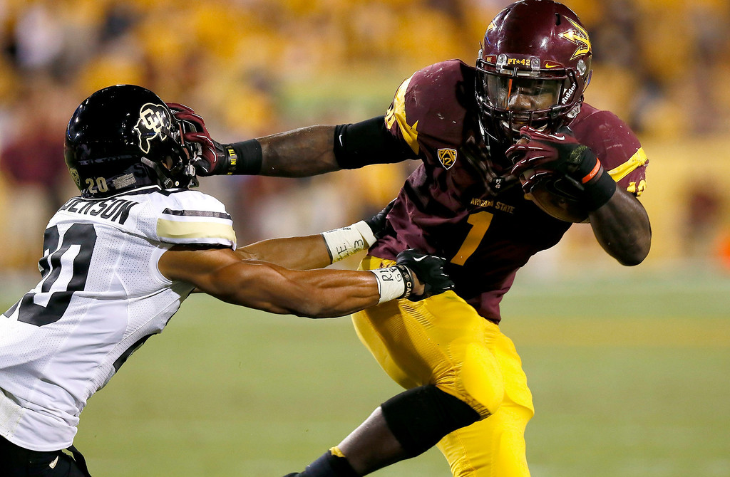. Arizona State\'s Marion Grice (1) stiff-arms Colorado\'s Greg Henderson while running with the ball during the first half of an NCAA college football game on Saturday Oct. 12, 2013, in Tempe, Ariz. (AP Photo/Ross D. Franklin)