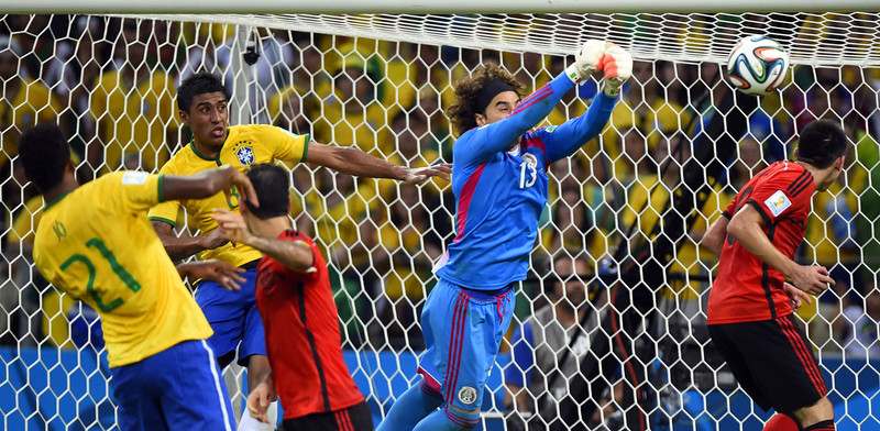 . Mexico\'s goalkeeper Guillermo Ochoa (2nd R) makes a save against an attempt at goal by Brazil\'s defender Thiago Silva (not seen) during a Group A football match between Brazil and Mexico in the Castelao Stadium in Fortaleza during the 2014 FIFA World Cup on June 17, 2014. (ODD ANDERSEN/AFP/Getty Images)