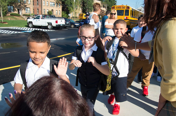 09/03/19 Wesley Bunnell | StaffrrPayton Castiglione, middle, walks past city officials and school administrators receiving high fives on her first day of school at Smalley School on Tuesday September 3, 2019.