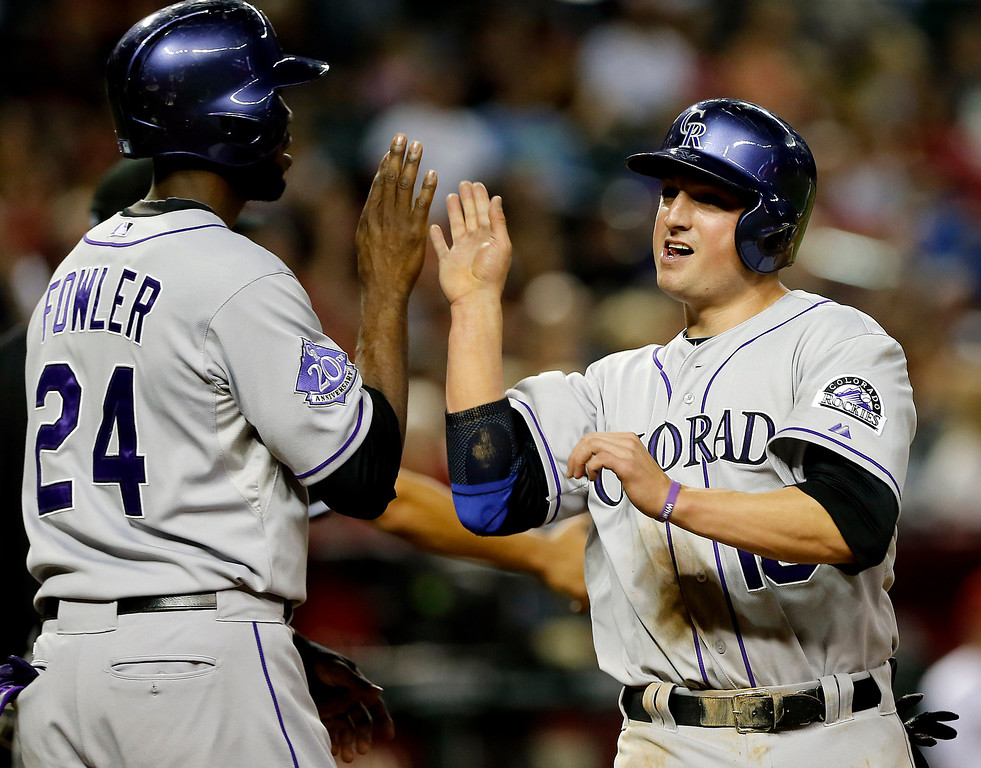 . Colorado Rockies\' Jordan Pacheco (15) and Dexter Fowler (24) score on a double by teammate Troy Tulowitzki during the fifth inning of a baseball game, Friday, April 26, 2013, in Phoenix. (AP Photo/Matt York)