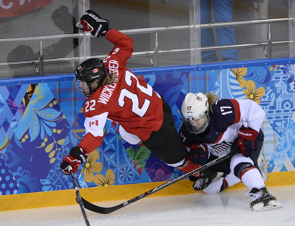 . US Jocelyne Lamoureux (R) hits Canada\'s Hayley Wickenheiser during the Women\'s Ice Hockey Group A match between Canada and USA at the Sochi Winter Olympics on February 12, 2014 at the Shayba Arena. AFP PHOTO / JONATHAN NACKSTRAND/AFP/Getty Images