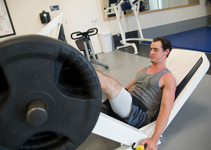 Student Joaquin Horton perform various exercises to keep up his strength in Dugan Wellness Center.