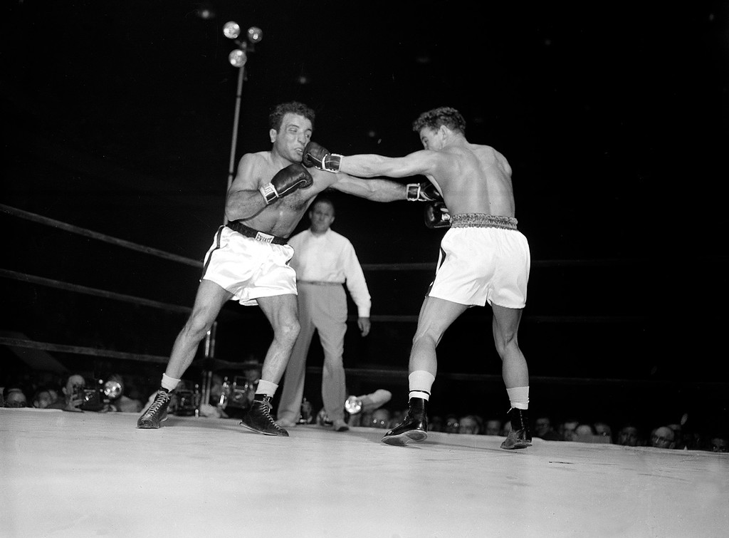 . Challenger Laurent Dauthuille, right, of France, connects with a long left to the face of Jake LaMotta in first round of their middleweight championship bout in Detroit, Mich., Sept. 13, 1950.  LaMotta won the title fight in the fifteenth round in a knockout.  (AP Photo)