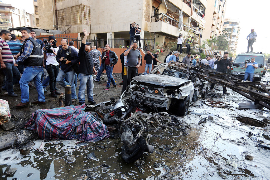. Lebanese people gather at the scene where two explosions have struck near the Iranian Embassy killing many, in Beirut, Lebanon, Tuesday, Nov. 19, 2013.  (AP Photo/Bilal Hussein)