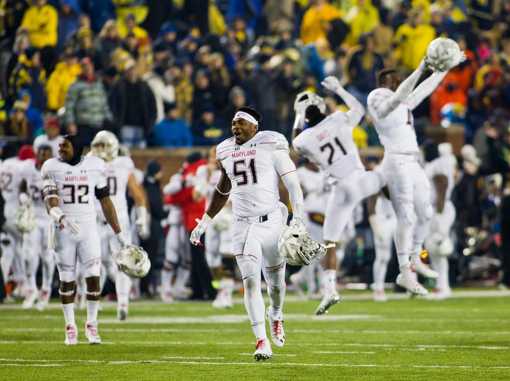 . Maryland linebacker Yannik Cudjoe-Virgil (51) celebrates on the field at the end of an NCAA college football game against Michigan in Ann Arbor, Mich., Saturday, Nov. 22, 2014. Maryland won 23-16. (AP Photo/Tony Ding)