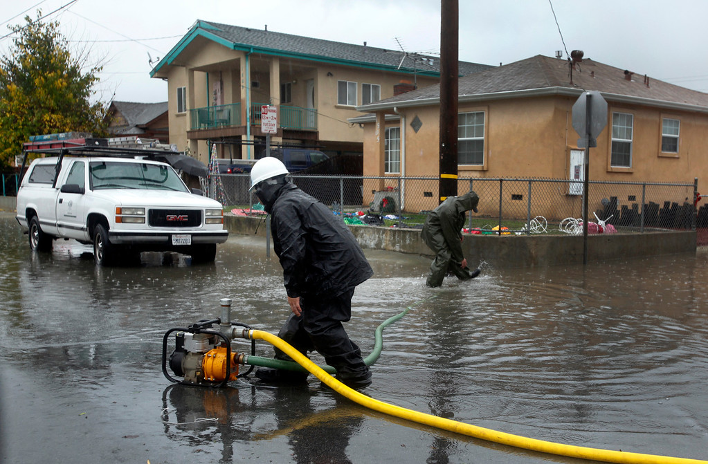 . Jeremy Cadena, left, and Duane Alcorn volunteer with their own pump to help fight rising waters in their neighborhood in Alviso, Calif., Thursday, Dec. 11, 2014. (Karl Mondon/Bay Area News Group)