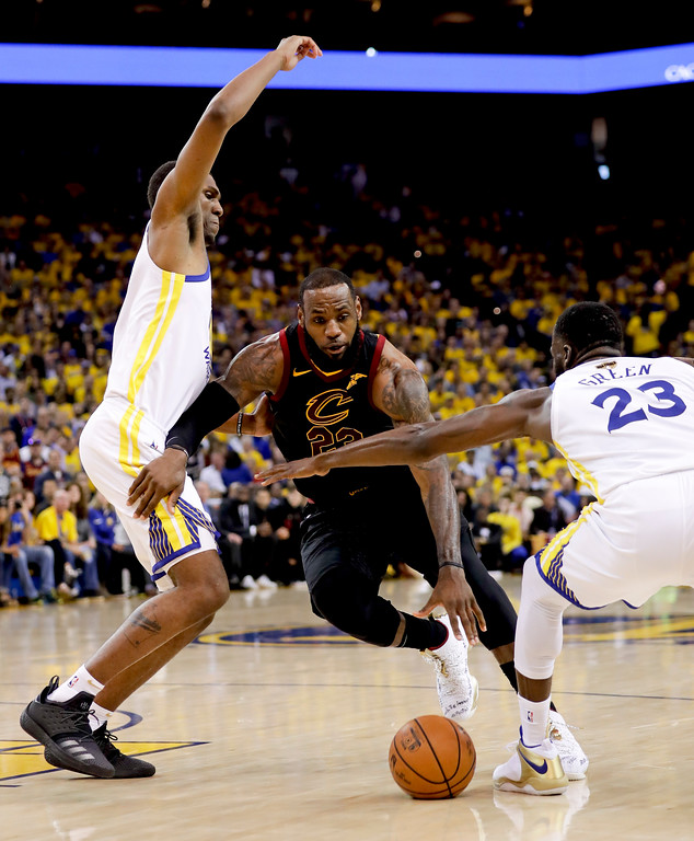 . Cleveland Cavaliers forward LeBron James, center, dribbles between Golden State Warriors forward Kevon Looney, left, and forward Draymond Green during the second half of Game 1 of basketball\'s NBA Finals in Oakland, Calif., Thursday, May 31, 2018. (AP Photo/Marcio Jose Sanchez)