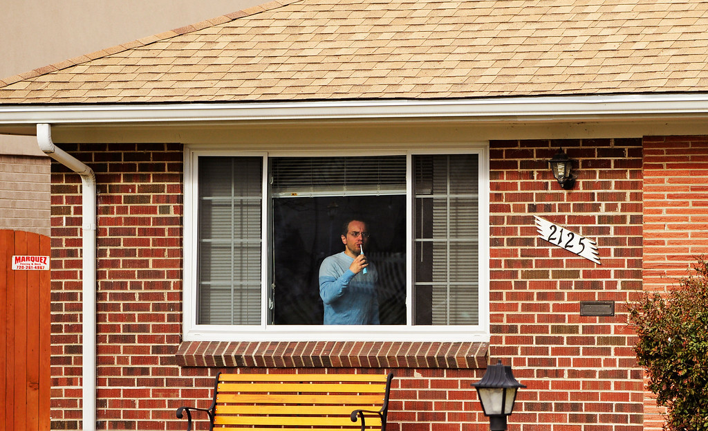 . A neighbor brushes his teeth as he watches Denver police investigate a homicide a cross the street at the 2100 block of South Saint Paul Street in Denver, Tuesday, April 15, 2014. A woman was found dead in a home near the University of Denver Monday night. (Photo by RJ Sangosti/The Denver Post)