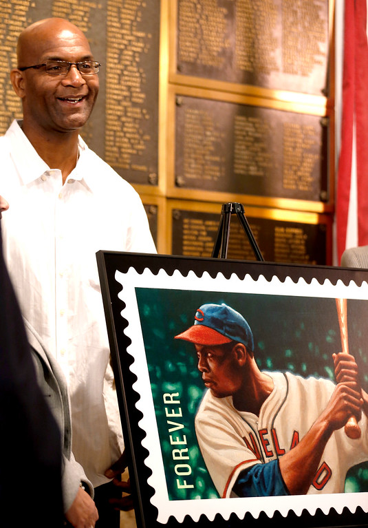 . Larry Doby, Jr., the son of the first black baseball player to play in the American League, stands next to a commemorative U.S. postage stamp in honor of his father, Larry Doby, Thursday, Aug. 23, 2012, in Paterson, N.J. The South Carolina-born Doby attended Eastside High School in Paterson, where he earned 11 varsity letters in several different sports. The Hall of Famer began his professional baseball career with the Newark Eagles of the Negro National League. After serving in World War II, Doby returned to the Eagles before joining the Cleveland Indians in 1947. (AP Photo/Julio Cortez)