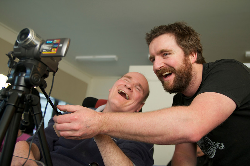 A Disability Support Worker assisting a man to operate a video camera.