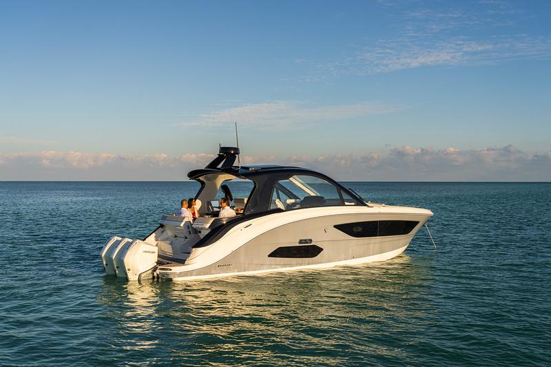 2021-Sundancer-370-Outboard-DAO370-lifestyle-starboard-stern-three-quarter-couple-friends-05788.jpg