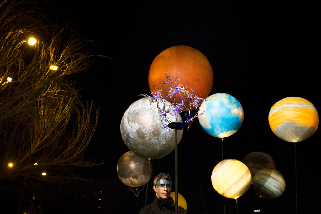 ". An artist performs with balloons depicting the solar system on a street as they march during ""Cabalgata de Reyes,\"" or the Three Wise Men parade, in Madrid, Thursday, Jan. 5, 2017. The traditional parade marks the eve of the Epiphany, a Christian holiday celebrating the story of the three wise men believed to have followed a bright star to offer gifts of gold, frankincense and myrrh to the newborn Jesus in Bethlehem. (AP Photo/Daniel Ochoa de Olza)"