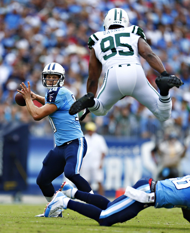 . NASHVILLE, TN - SEPTEMBER 29:  Jake Locker #10 of the Tennessee Titans looks to throw a pass while under pressure from Antwan Barnes #95 of the New York Jets at LP Field on September 29, 2013 in Nashville, Tennessee.  (Photo by Wesley Hitt/Getty Images)
