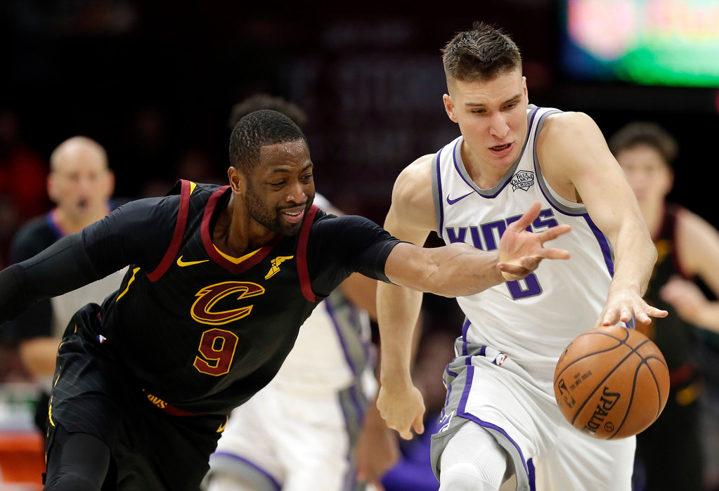 . Sacramento Kings\' Bogdan Bogdanovic (8), from Serbia, and Cleveland Cavaliers\' Dwyane Wade (9) battle for a loose ball in the second half of an NBA basketball game, Wednesday, Dec. 6, 2017, in Cleveland. (AP Photo/Tony Dejak)