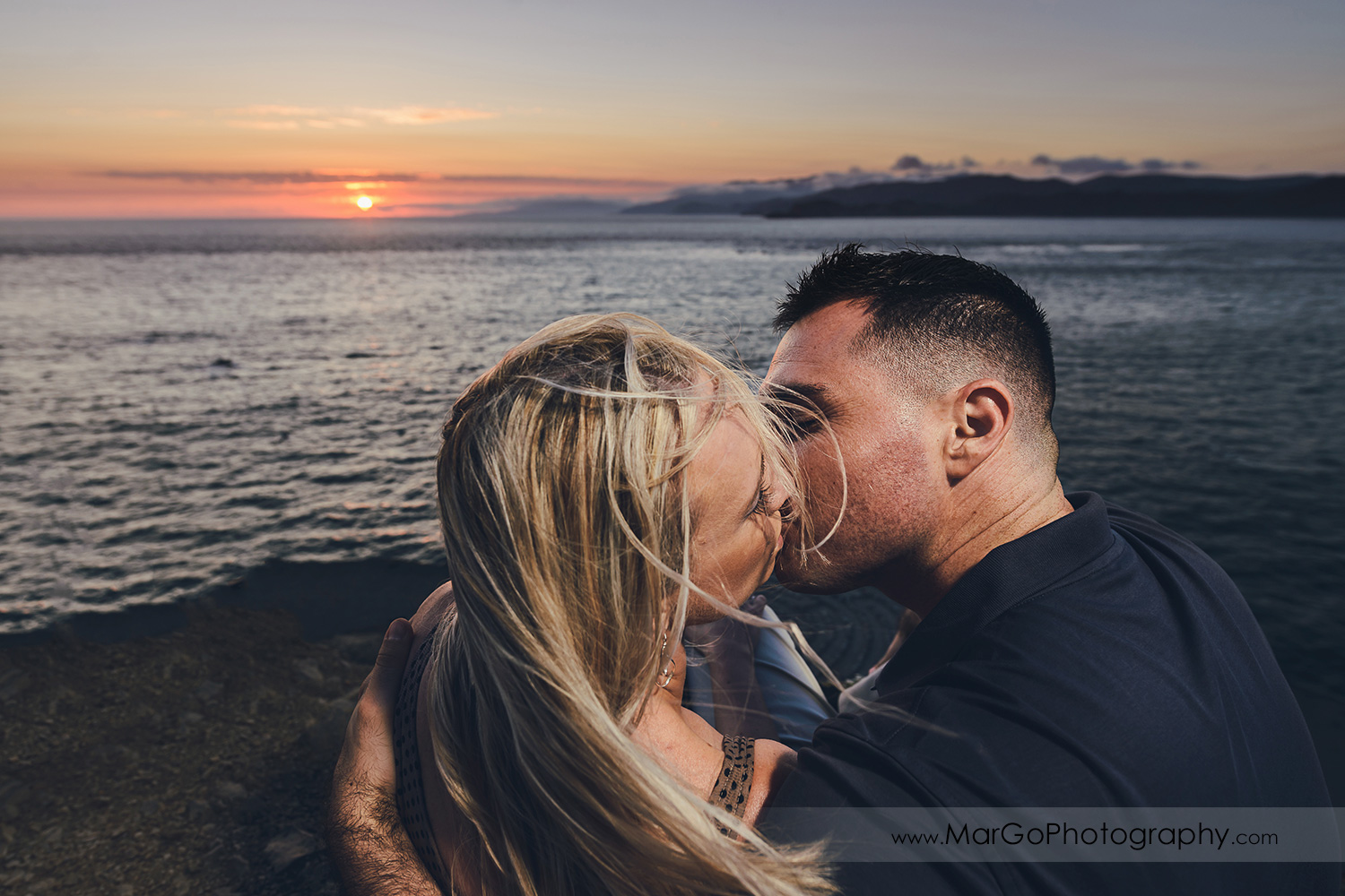 man in navy blue shirt and woman in brown tunic kissing above the stone labyrinth during sunset engagement session at San Francisco Lands End