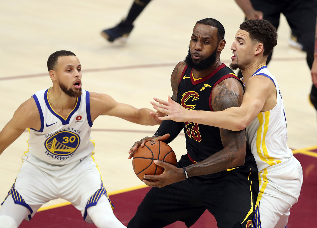 . Cleveland Cavaliers\' LeBron James (23) is defended by Golden State Warriors\' Klay Thompson and Stephen Curry (30) during the first half of Game 4 of basketball\'s NBA Finals, Friday, June 8, 2018, in Cleveland. (AP Photo/Carlos Osorio)