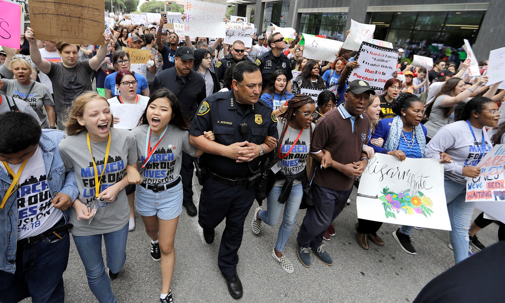 . Houston Police Chief Art Acevedo, center, Houston Mayor Sylvester Turner, right, and Rep. Sheila Jackson Lee, D-Texas, right in blue, join demonstrators during a March for Our Lives protest for gun legislation and school safety Saturday, March 24, 2018, in Houston. Students and activists across the country planned events Saturday in conjunction with a Washington march spearheaded by teens from Marjory Stoneman Douglas High School in Parkland, Fla., where 17 people were killed in February. (AP Photo/David J. Phillip)