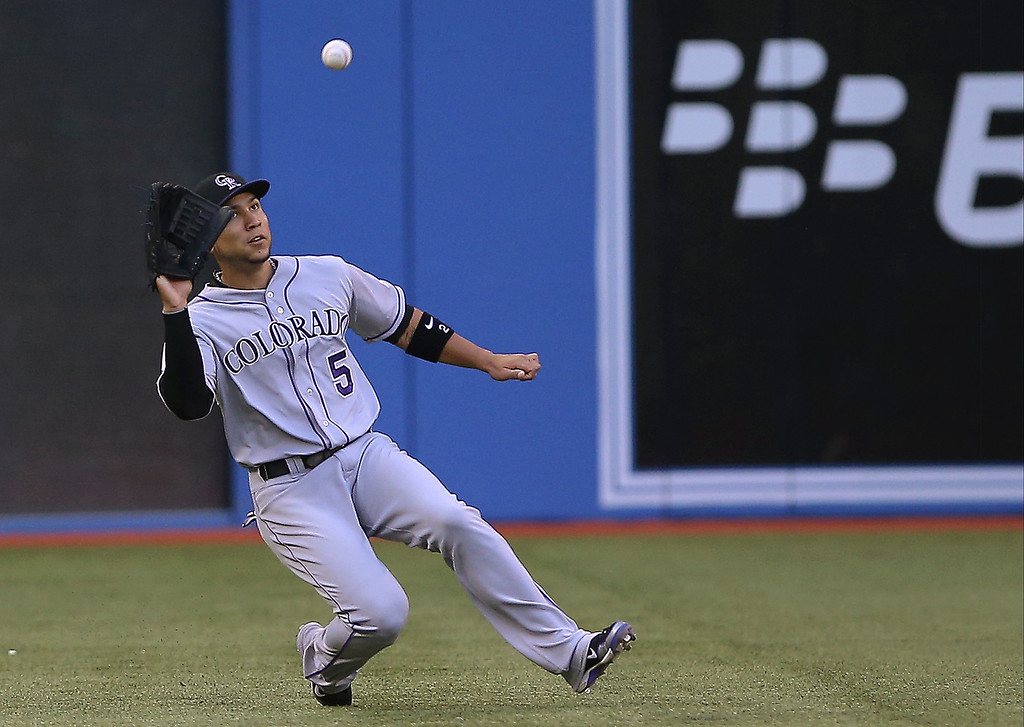 . Carlos Gonzalez #5 of the Colorado Rockies makes a sliding catch in the first inning against the Toronto Blue Jays on June 19, 2013 at Rogers Centre in Toronto, Ontario, Canada. (Photo by Tom Szczerbowski/Getty Images)