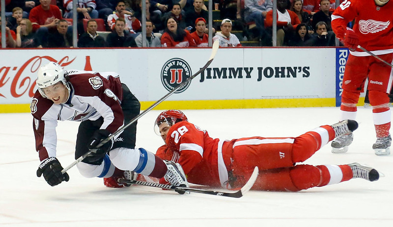 . Detroit Red Wings defenseman Carlo Colaiacovo (28) uses his stick to trip Colorado Avalanche center Matt Duchene (9) in the third period of an NHL hockey game Monday, April 1, 2013, in Detroit. The Red Wings defeated the Avalanche 3-2. (AP Photo/Duane Burleson)