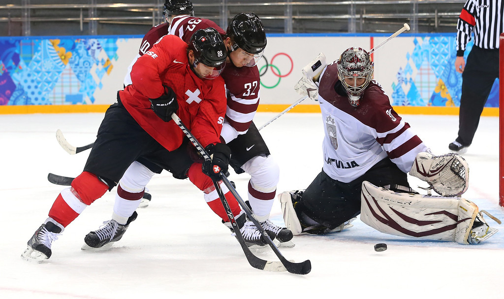. SOCHI, RUSSIA - FEBRUARY 12: Kevin Romy #88 of Switzerland shoots against Arturs Kulda #32 and Edgars Masalskis #31 of Latvia in the third period during the Men\'s Ice Hockey Preliminary Round Group C game on day five of the Sochi 2014 Winter Olympics at Shayba Arena on February 12, 2014 in Sochi, Russia.  (Photo by Martin Rose/Getty Images)