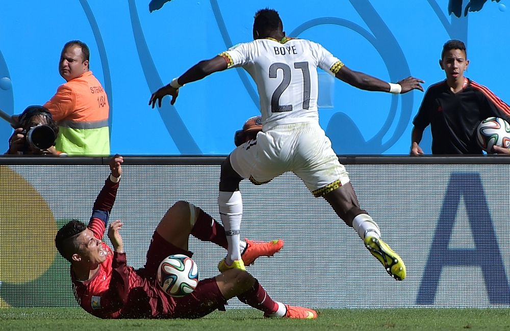 . Portugal\'s forward and captain Cristiano Ronaldo\'s mknee is injured by Ghana\'s defender John Boye\'s tackle during the Group G football match between Portugal and Ghana at the Mane Garrincha National Stadium in Brasilia during the 2014 FIFA World Cup on June 26, 2014.  (GABRIEL BOUYS/AFP/Getty Images)
