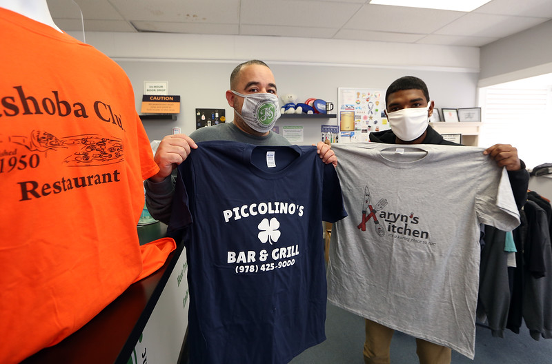 Jose Banchs of Shirley, left, owner of J & S Business Products, and employee Izeaha Harmon Ayer, show some of the tee shirts the company is making for other small businesses during the pandemic. (SUN/Julia Malakie)